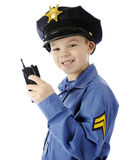 Walkie Talkie Cop Closeup. Closeup image of a happy young boy using his walkie talkie while in his police uniform.  On a white background Royalty Free Stock Image