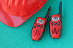 Helmet safety with walkie talkie. Walkie talkie with safety helmet on a green background Stock Photo