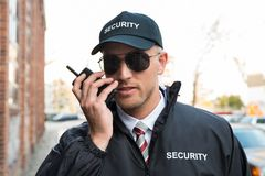 Walkietalkie de Talking On do agente de segurança fotografia de stock