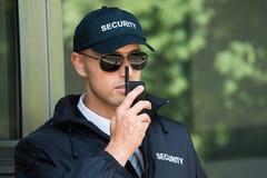 Walkietalkie joven de Talking On del guardia de seguridad imagen de archivo