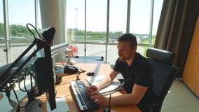 Walkietalkie y ordenador del uso del empleado del servicio del camino dentro de la sala de control moderna Fondo de la carretera