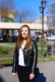 Walkign de la mujer joven en ciudad y chaqueta de cuero que lleva Fotografía de archivo