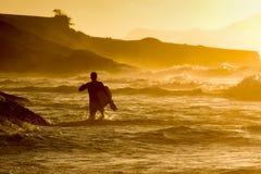 Walkimg di Bodyboarder nell'acqua fotografie stock