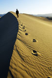 Walking. Person walking off into the distance on a sand dune leaving behind footsteps Stock Image