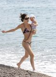 Walking. Photo of slim female in bikini walking down seashore with adorable infant at summer Stock Image