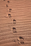 Walking across the desert in boots Stock Photography