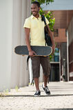 Walking African American Student. Young African American student walking to class with skateboard Royalty Free Stock Photos