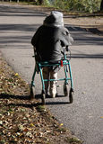 Walking aid. Old woman getting some sun sitting on her walking aid royalty free stock photo