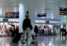 Walking in an airport. Man with suitcase walking in an airport-motion blur Royalty Free Stock Image