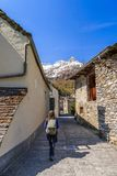 Walking on alley in Sonogno. Asian tourist woman with her backpack walks on typical alley among traditional stone houses in Sonogno in Locarno district Stock Image