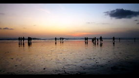 Walking alone at the kuta beach with beautiful sunset behind, Bali.