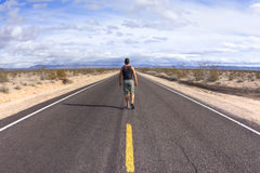 Walking alone on a lone desert highway Royalty Free Stock Photos