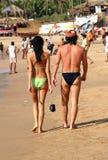 Walking along a beach. Young couple walking along a beach - Anjuna village, Goa, India royalty free stock photography