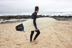 Walking along the Beach with Surfboard Stock Image
