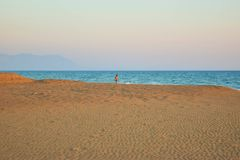 Walking along the beach. Walking along the beautiful sandy Kaiafas beach at sunset, Greece stock image
