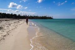 Walking along pristine sandy beach Royalty Free Stock Photos