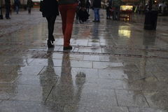 Walking along wet pavement street. Rain in the city. Royalty Free Stock Photos