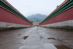 Experience ancient Chinese palace. In Heng Dian World Studios, one girl walking through corridor of ancient Chinese walls Royalty Free Stock Images