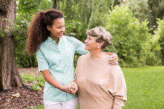 Walking around with elder. Nurse is walking around with elder lady royalty free stock image