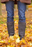 Walking in autumn. Image of legs in boots on the autumn leaves. Feet shoes walking in nature Royalty Free Stock Image