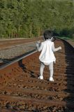 Walking away. Little girl walking along the railway Royalty Free Stock Photos