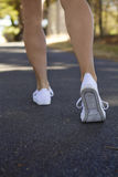 Walking away woman exercising outdoors. Close up of woman's legs walking away from camera Royalty Free Stock Photos