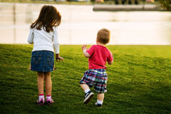 Walking With Baby Brother. A little girl walks tentatively next to her baby brother as he totters up a hill in a park. The two are walking towards a pond on a Royalty Free Stock Photos