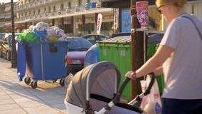 Walking with baby in the street with full dumpsters. NEA KALLIKRATIA, GREECE - AUGUST 12, 2017: Woman with baby with model release in pram walking in the street stock footage
