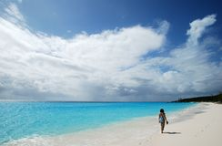 Walking In The Bahamas. The girl walking along empty beach on Half Moon Cay, The Bahamas Stock Photos