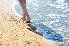 Walking  barefoot on the beach Royalty Free Stock Image