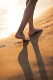 Walking barefoot on the beach Stock Photography