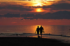 Walking on the beach. A couple enjoying a romantic walk on the beach at sunset Stock Image