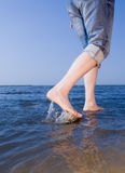 Walking on the beach. Long legs of tall lady walking in water by the north sea beach in the summer Stock Photos