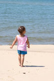 Walking on the beach. A Little girl walking alone on the beach Stock Images