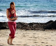 Walking on the beach. Young mother on the beach with her child Royalty Free Stock Photos