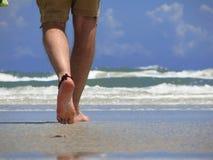 Walking On The Beach. Closeup of a man's leg walking on new smyrna beach, florida. shallow DOF stock photo