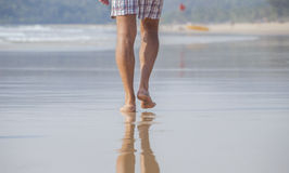 Feet of the man. Walking on the beach in day time Stock Photo