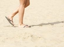 Walking on beach with flip flops Stock Images