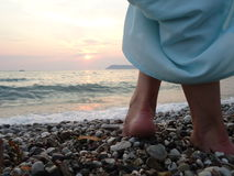 Walking on the beach. Girl goes on the beach, walking on the sand with bare feet and walk toward the water Royalty Free Stock Photos