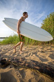 Walking at the beach and holding a surfboard Royalty Free Stock Images
