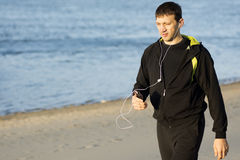 Walking on beach. The man in sportswear with earphones is walking on the beach Stock Images