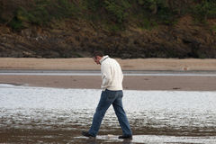 Walking on the Beach. Man striding along the beach in devon, UK. Looks like he is thinking about something Stock Photos