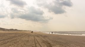 Walking at the beach of northern hollad on a partly cloudy day. royalty free stock image