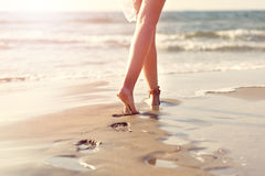 Walking on the beach at sunset leaving footprints over sands Royalty Free Stock Photo