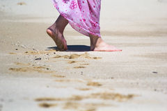 Walking on a beach. A woman wearing a sarong walking on a sandy beach Royalty Free Stock Photography