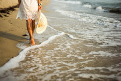 Walking on the beach. Young woman walking on the beach early in the morning Royalty Free Stock Image