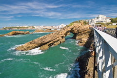Walking on beautiful footbridge leading to rocher de la vierge on atlantic coastline with cliffs and turquoise ocean in biarritz, Royalty Free Stock Image