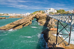 Walking on beautiful footbridge leading to rocher de la vierge on atlantic coastline with cliffs and turquoise ocean in biarritz, Stock Image