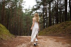 Walking Beautiful young blonde woman forest nymph in white dress in evergreen wood stock photography