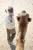 Walking Beduin. Douz, Kebili, Tunisia - September 17, 2012 : Beduins leading tourists on camels at the Sahara desert on September 17, 2012 in Douz, Kebili stock photo